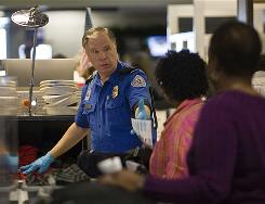 A TSA officer screens fliers at Dallas/Fort Worth International Airport on Dec. 27.