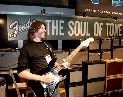 Fender's Rick Heins rocks out at the company booth during a recent trade show in Anaheim, Calif., with the help of the new G-DEC amp from Fender.