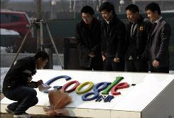A man looks at a note left in support of Google outside its Beijing offices as others pose for photos. The search giant has threatened to pull out of China because of Internet restrictions.
