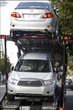 Josh Walker drives a Highlander hybrid SUV off a truck at a dealership in Seattle on Wednesday. Toyota Motor has halted sales of some of its top-selling models.
