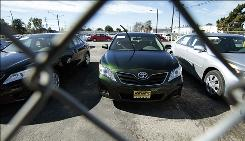 Toyota models that have been withdrawn for sale, identified by stickers on the windshield or by a single windshield wiper pointing skyward, or both, are seen at a storage lot for Keyes Toyota in the Van Nuys area of Los Angeles.