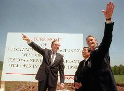 Sen. Jay Rockefeller, D-W.Va., left, Toyota President Hiroshi Okuda and West Virginia Gov. Gaston Caperton celebrate at the Toyota plant in Buffalo, W.Va., on May 9, 1996.