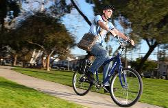 Paul Kelleher rides his electric bike through a park in the Valley Village district in Los Angeles.
