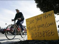 A bicyclist passes a sign offering home loan modifications on a street corner in Stockton, Calif., on March 11, 2009.