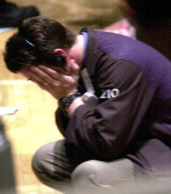 A trader on the floor of the New York Stock Exchange holds his head in his hands.