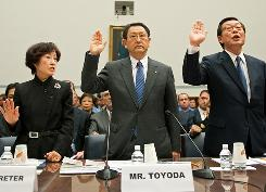 As the official interpreter stands to the left, Toyota Motor CEO Akio Toyoda (center) and North American CEO Yoshimi Inaba are sworn in to testify at the U.S. House Oversight and Government Reform Committee.