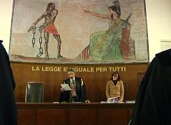 Italian judge Oscar Magi, with an aide beside him, gives a verdict in a Milan courtroom on Wednesday in this image taken from video.