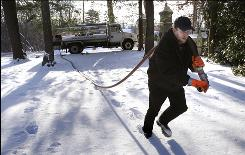 Jason Kilpatrick of Wholesale Fuel hauls a hose across a Framingham, Mass., yard in January to deliver heating oil.