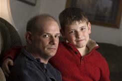 Terry Becker and his 10-year-old son Nate pose Feb. 24, 2010, in their Milton, Wis home. Terry Becker says he racked up $25,000 in medical debt for the boy, which has left him with bad credit.