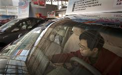 Robin San inspects a new car at a Chery dealership in Beijing. With a 2-year-old daughter, he wants to upgrade to a newer, safer model.
