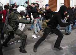A riot policeman tries to catch a protester during a rally turned violent in central Athens on Friday.