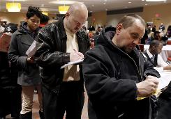 Sharon Phillips, left, William Wright, center, and Tim Paliwoda, right, all of Detroit, fill out applications while attending a job fair in Detroit.
