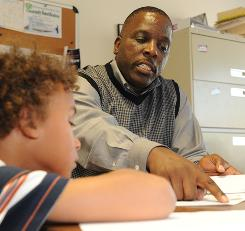 Courtney Stewart, who was in foster care, set up a non-profit group to help kids in his old Washington neighborhood. Here he's helping Jason Hickson, 8, with his homework. See story below.
