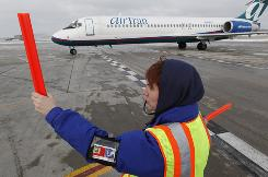 Elizabeth Weiss directs an arriving AirTran flight to its gate in Milwaukee.