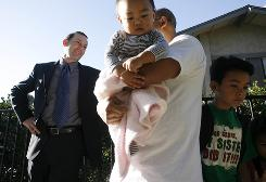 Property owner and buyer Leonard Baron, left, talks with his tenants, Joseph Munar, daughter Arabella, 1, and son Joseph, 9, outside one of the homes Baron owns in Chula Vista, Calif.