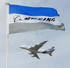 An Airbus A380 takes flight behind a Boeing banner at the Paris air show.