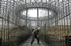 A construction crewmember works at a site in Taiyuan, in north China's Shanxi province. China's rapid escalation in real estate values has raised concern about an overheated market.