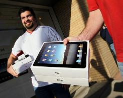 A smiling Victor Garza, left, and Brandon Davenport on Saturday are the first to walk out of an Apple Store in Dallas with iPads in hand.