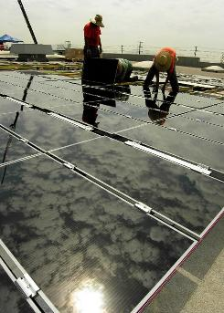 Workers install solar panels on a warehouse rooftop in California. Eventually there will be 33,700 on the structure.