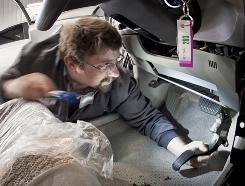 Dusty Thomas, a technician at Camelback Toyota in Phoenix, installs a new gas pedal. The new pedals are significantly shorter than the old ones.
