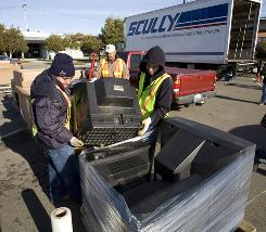Waste management workers unload CRT monitors and other electronic waste during a free recyling event at El Cerrito, Calif., in January 2009.