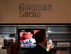 Financial professionals work in the Goldman Sachs booth on the floor of the New York Stock Exchange at the end of the trading day in July 2009.