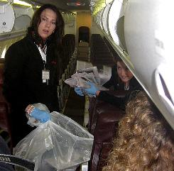 Horizon Air flight attendants Rena Nelson, left, and Jillian Zurfluh demonstrate how they separate recyclables on an aircraft at Seattle-Tacoma International. 