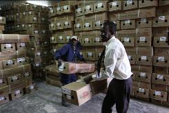 Workers for Van de Berg Flowers in Kenya stack boxes of flowers waiting to ship in the storeroom Monday.