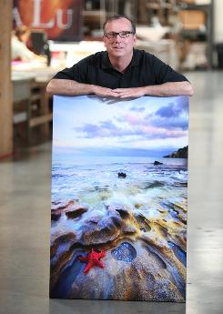 John Doe, founder of Your Photo on Canvas, is photographed with a photo that's been made into a canvas print. The company has a deal with retail giant Costco to sell such canvas prints. At bottom left, Silvestre Esparza tacks a print onto a frame. At bottom right, Doe works with a print.