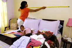 Cheryl Stewart lost her job a year ago but has started shopping again, including for new decor for her 4-year-old daughter's room. Here, she measures the wall, while 5-month-old daughter, Peyton, plays on the bed.