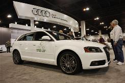 Buyers survey a 2010 Audi A3 TDI wagon on display at the Denver auto show in Denver.