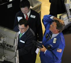 Traders on the floor of the New York Stock Exchange watch one of the electronic boards showing a steep decline in the markets Thursday, May 6, 2010.