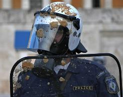 A riot policeman is splattered with iced coffee in Athens on Thursday.