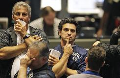 Traders react in the S&P 500 futures pit at the CME Group in Chicago near the close of markets on Thursday. The stock market has had one of its most turbulent days ever.