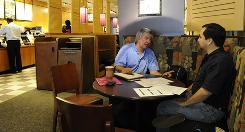 Robert Korzeniewski, left, mentors job seeker Robert Mendez on his search. Korzeniewski is the volunteer leader at the Career Network Ministry at the McLean Bible Church in Northern Virginia. He holds sessions in local restaurants and oversees the CNM's weekly meeting.
