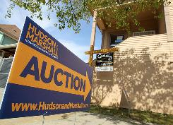 A sign advertising an auction is posted in front of a foreclosed home in Oakland, California.