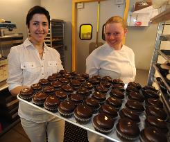 Tracy Wilson, CEO of Red Velvet Cupcakery, left, and Stephanie MacGlaughlin show off a tray full of the store's specialties.