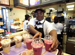 Ella Howard sets up a tray of freshly made wild berry smoothies, right, and caramel frappes to be given away as samples to customers at a McDonald's in Detroit on May 10.