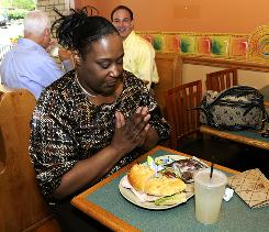 Lisa Matthews says a short prayer before lunch. She said she paid the full suggested price, and likes the idea of the cafe.