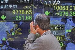 A looks at an electronic stock board in Tokyo, in this file photo.
