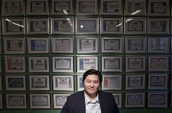 Lance Lee, CEO of OneShare.com, in front of a wall of paper stocks in his San Francisco office.