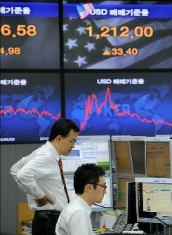 Foreign currency dealers monitor exchange rates at the Korean Exchange Bank in Seoul on Tuesday.