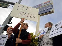 Danielle Bridgeford, left, Bob Fulkerson and William Puchert hold up signs against BP in front of an Arco gas station in Reno on Thursday.