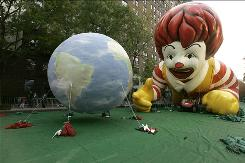 An uptick in McDonald's sales was spurred partly by increasing global sales. Here, Ronald Mcdonald eyes an earth balloon the day before Macy's 81st Annual Thanksgiving Day Parade.