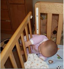 A doll is used to show how a baby can get stuck in a Child Craft drop-side crib.