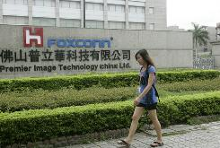 A Chinese worker walks past a Foxconn factory in an industrial district of Foshan City, southern China's Guangdong province on June 17, 2010. 