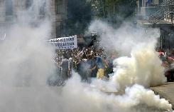 Greek protesters are seen through tear gas near the Greek parliament building on June 29, 2010.