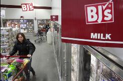 Shoppers at a BJ's Wholesale store location in Dedham, Mass., make their way down a dairy aisle.