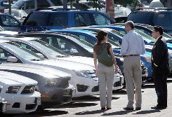 Customers shop for cars at the Star Ford car dealership on November 16, 2009 in Glendale, Calif.