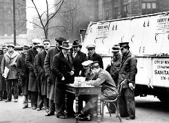 """In this Jan. 3, 1934 file photo, men line up in front of City Hall to apply for jobs cleaning away snow in New York City during the Great Depression. A sign attached to the parked snow-removal truck reads, """"Laborers Wanted."""""""